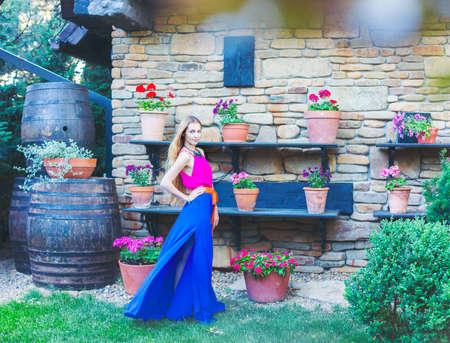 Bella donna bionda in vestito lungo colorata all'aperto