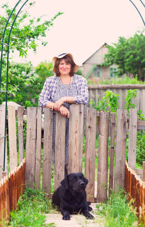 Happy middle age woman in the garden with her labrador dog photo