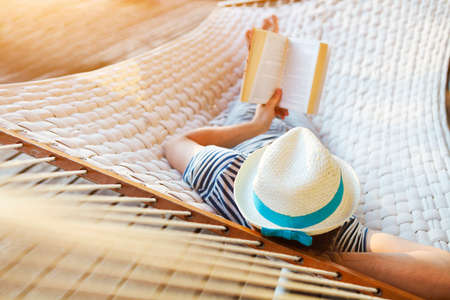 pies descalzos: Momentos de pereza. El hombre en el sombrero en una hamaca con el libro en un d�a de verano Foto de archivo