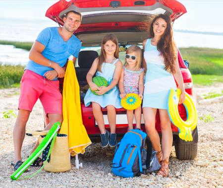 一个微笑的家庭的画象有两个孩子的在海滩乘汽车