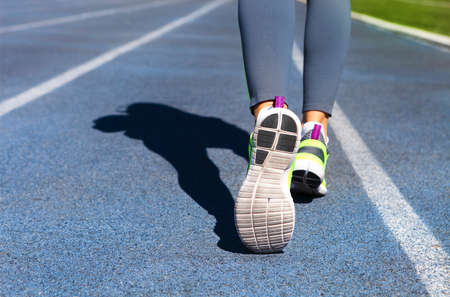 female athlete: Athlete runner feet down stadium track. Closeup on female shoe and legs. Woman summer fitness workout. Jogging, sport, healthy active lifestyle concept.