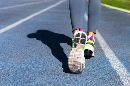 mujer deportista: pies de atleta corredor abajo pista del estadio. Primer en el zapato y las piernas femeninas. Verano de la mujer de la aptitud del entrenamiento. Footing, deporte, sano concepto de estilo de vida activo. Foto de archivo
