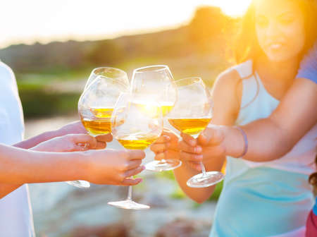 garden parties: Celebration. People holding glasses of white wine making a toast. Sunset summer party