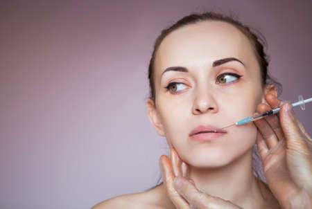 inyeccion: Mujer bonita joven que consigue la inyección de cosméticos en la cara como una parte del tratamiento de la clínica. Medicina, salud y el concepto de belleza