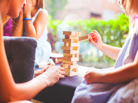 tower: Happy mother with two children playing the wooden blocks tower at home Stock Photo