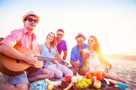 guitarra: Amigos que se sientan en la arena en la playa en círculo. Un hombre está tocando la guitarra