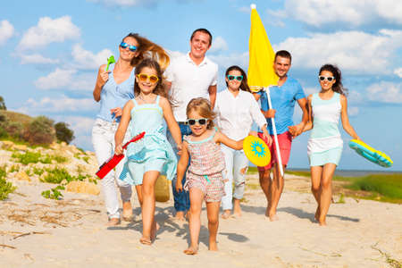 Multiracial group of friends with children running at the beach 스톡 콘텐츠