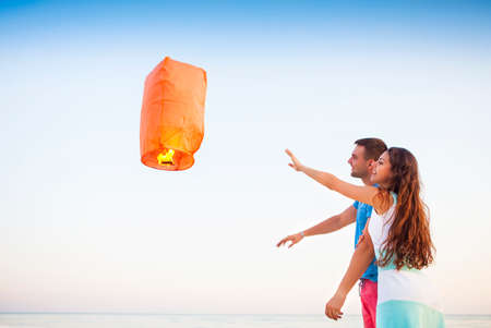 sky lantern: Young couple start a red Chinese sky lantern in the dusk near the sea