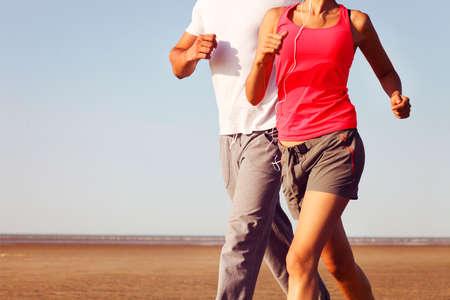 hombres corriendo: Pares que activan el exterior, la formación corredores trabaja al aire libre en la naturaleza contra el cielo azul con la luz del atardecer. De cerca Foto de archivo