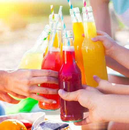 take away: Group of friends holding drinks at the summer picnic. Close up