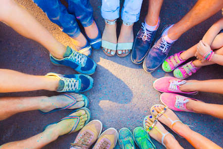 worshipers: Friends putting their feet together in a sign of unity and teamwork. Holi colors festival. Friendship concept