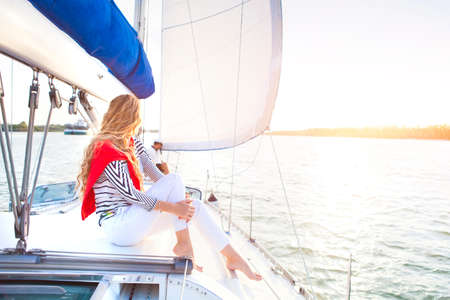 voilier ancien: Jeune couple sur un bateau à voile au coucher du soleil d'été Banque d'images