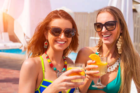 beach wear: Happy female friends with beverages on summer party near the pool