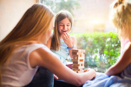 children at play: Happy mother with two children playing the wooden blocks tower at home Stock Photo