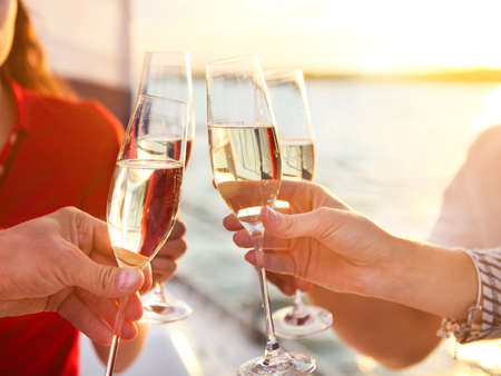cruising: Happy friends with glasses of champagne on yacht. Vacation, travel, sea and friendship concept. Closeup. Stock Photo