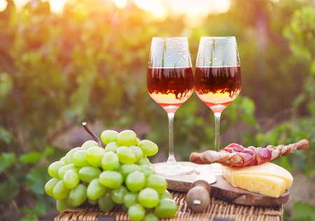 pan y vino: Dos vasos de vino rosado con pan, carne, uva y queso en el fondo del viñedo Foto de archivo