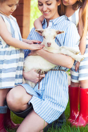 happy family nature: Happy mother and her daughters with baby goats on the countryside Stock Photo