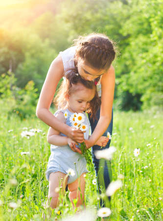 latin child: Portrait of two happy sisters in the daisy spring field Stock Photo