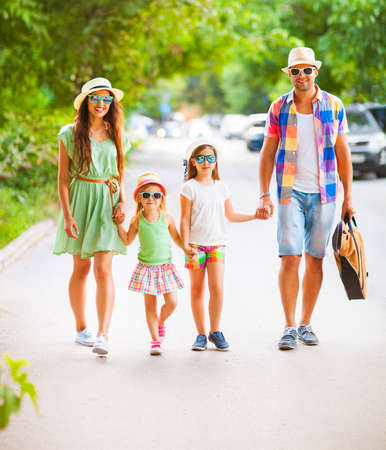 Happy young family walking with guitar spending carefree time together. Travel and holiday concept
