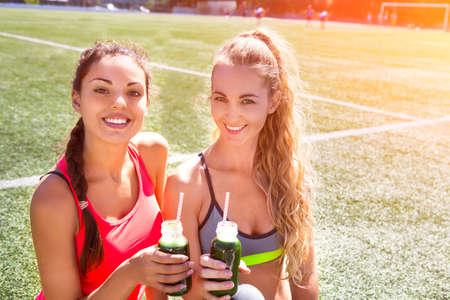 dieta sana: Dos mujeres felices beber batido de verduras después de entrenamiento de la aptitud que se ejecuta en el estadio. La aptitud y el concepto de estilo de vida saludable