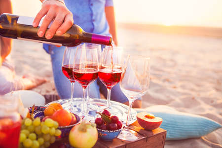 beach man: Group of happy friends having red wine on the beach. Sunset beach party