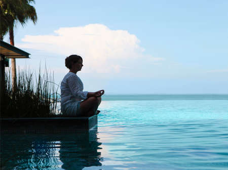 body scape: Silhouette of attractive woman sitting in meditating position by the pool Stock Photo
