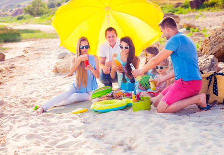 Friends sitting on the sand at the beach at the summer picnic. Green bucket with lemonade