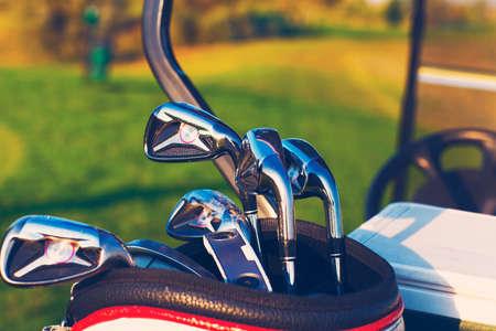 putter: Golf clubs drivers over green field background. Summer sunset Stock Photo