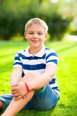 niños sentados: Niño sentado en la hierba con la sonrisa en el parque de verano