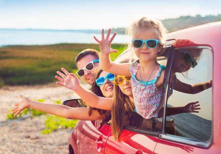 Portrait d'une famille souriante avec deux enfants à la plage dans la voiture. Vacances et le concept de Voyage