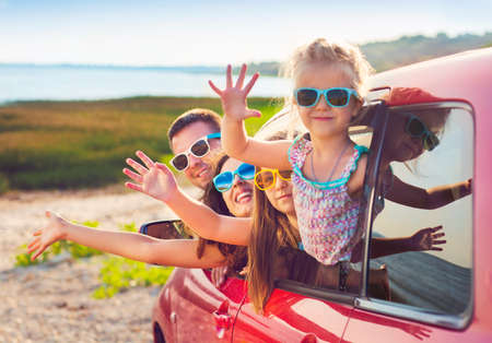 Portrait of a smiling family with two children at beach in the car.  Holiday and travel concept Stock fotó - 54379909