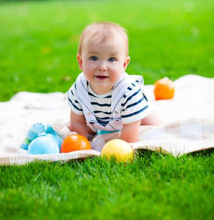 嬰兒: 特寫人像微笑的男嬰玩戶外的 版權商用圖片