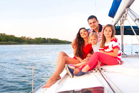 family time: Beautiful happy family with two daughters having great time at the yacht at summertime. Travel and vacation concept Stock Photo