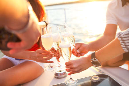 boat party: Happy friends with glasses of champagne on yacht. Vacation, travel, sea and friendship concept. Closeup. Stock Photo