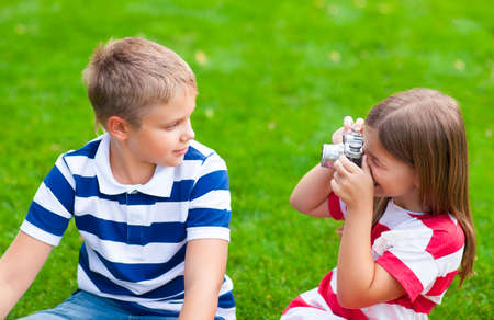 boy beautiful: Young photographers. Pretty little brother and sister playing with a camera in summer park