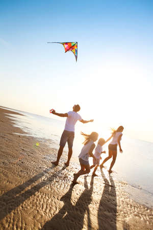 Happy young family with two kids with flying a kite on the beach 스톡 콘텐츠