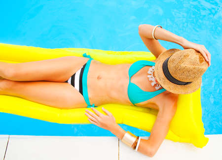 tanned body: Young pretty woman with perfect tanned body lying on yellow air mattress in the pool Stock Photo