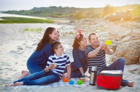 selfy: Family of five doing selfy at the picnic on the beach. Summer vacation concept