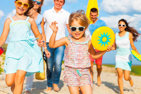 Multiracial group of friends with children walking at the beach 스톡 콘텐츠