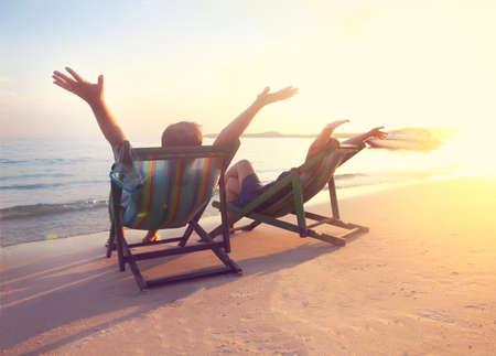 koh samet: Happy couple sitting at sun chairs on the beach of Koh Samet at sunset, Thailand