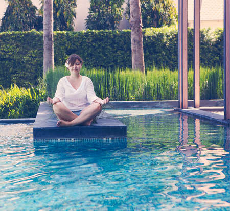 body scape: Portrait of attractive woman dressed in white sitting in meditating position by the pool