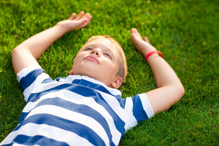 lay down: Little boy lay down on the grass with smile Stock Photo