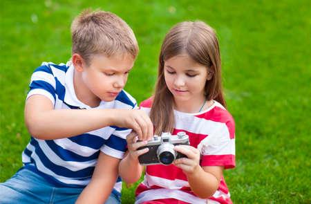ojos verdes: jóvenes fotógrafos. Bastante poco hermano y hermana jugando con una cámara en el parque de verano Foto de archivo