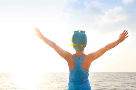 swim cap: Happy little girl in a bathing suit, swim cap, goggles at the beach Stock Photo