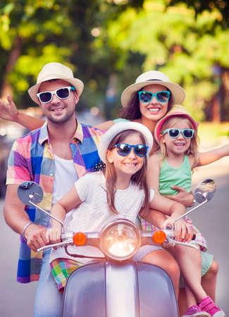 Familia joven feliz que monta una vespa de la vendimia en la calle con sombreros y gafas de sol. Vacaciones y el concepto de viaje Foto de archivo