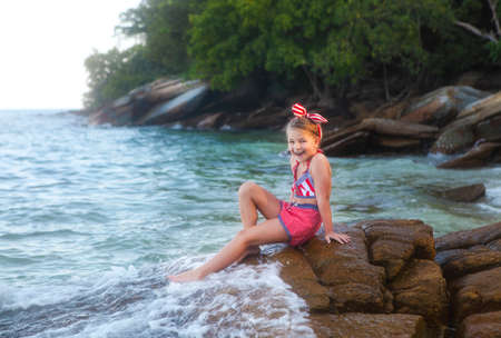 Happy little cute girl wearing retro swimsuit at the beach Stock Photo