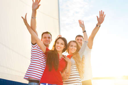 party friends: Smiling friends on yacht deck and greeting. Travel and vacation concept Stock Photo