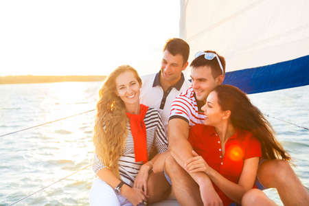 sail: Smiling friends on yacht deck and greeting. Travel and vacation concept Stock Photo
