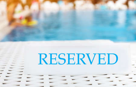 reserved sign: Reserved sign on the summer pool background. Vacation concept Stock Photo