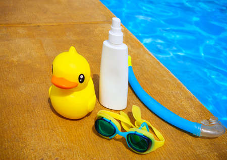 suncream: Suncream, snorkel, goggles and yellow rubber duck near the swimming pool. Vacation concept